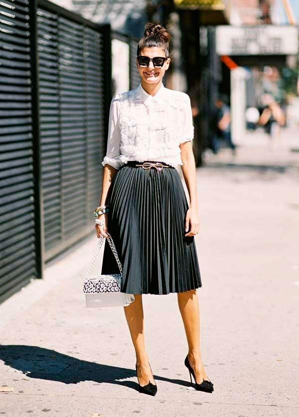 Giovanna Battaglia usa camisa branca e saia plissada com scarpin preto