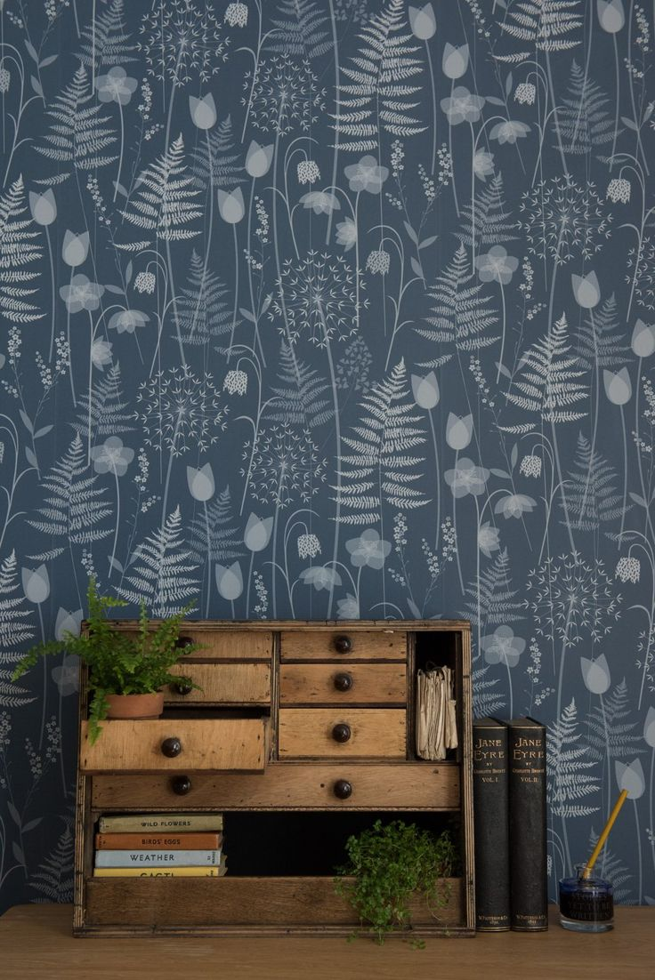Charlotte's Garden in 'Inkwell', a deep inky blue by Hannah Nunn - a wallpaper inspired by the flowers in bloom in the Brontë Parsonage garden around the time of Charlotte Brontë's birthday. It features ferns, alliums, forget-me-nots, hellebores, fritillaries and tulips. A beautiful  surface pattern design of spring flowers. Show here with a lovely set of old wooden drawers and some antiquarian Jane Eyre books. https://www.hannahnunn.co.uk/collections/wallpaper