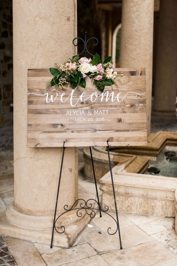 wood welcome board is dressed with a loose cluster of cluster of vendela rose, polo rose, peach stock, white wax flower, pink majolik spray rose, lemon leaf, almond blooms & seeded eucalyptus