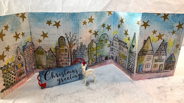 I was inspired by Rubber Dance's Textured Houses to make a mini folder in ATC size. I started by sticking Tim Holtz tissue wrap on as background.  Then it all got a layer of white gesso.  I stamped the houses and the stars, which were embossed with gold powder.  With distress ink and crayons I coloured the sky and the street.  The houses are highlighted with Prismacolor.
