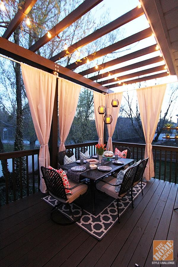 The outdoor curtains add a bit of privacy and elegance to this backyard deck. The lights strung on the pergola complete the picture. Click through to learn more about Jen's deck makeover.