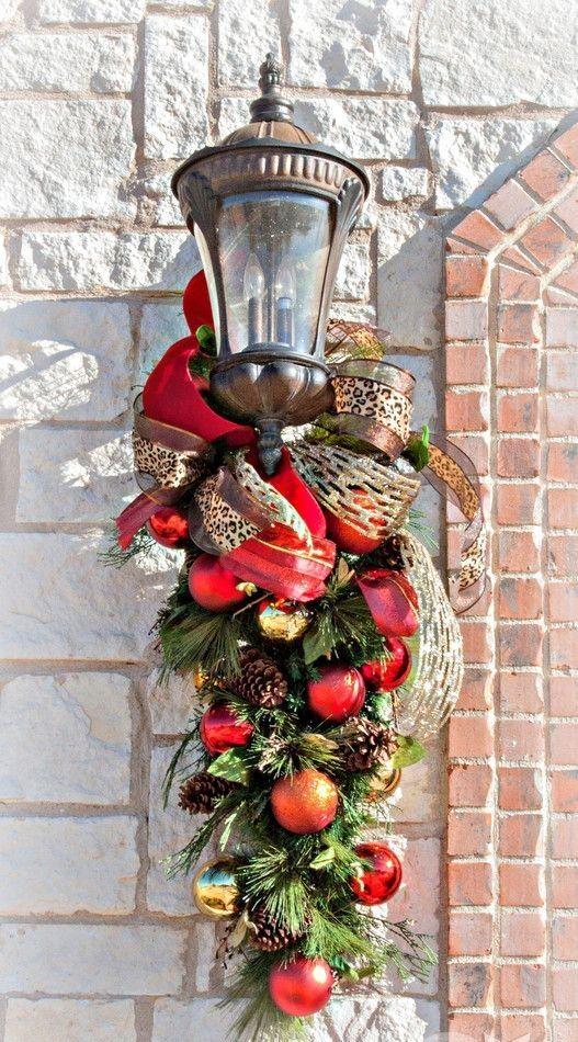 Un farol de entrada decorado con ramas de pino bolas y diferentes lazos.