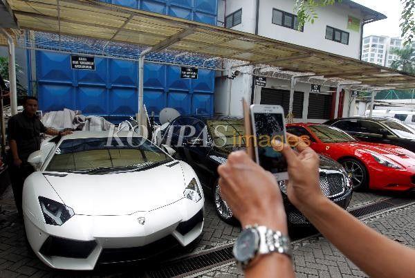 Warga berfoto di samping mobil-mobil mewah milik Tubagus Chaeri Wardana alias Wawan yang disita Komisi Pemberantasan Korupsi (KPK), diparkir di kompleks Gedung KPK, Jakarta Selatan, Selasa (28/1/2014). KPK telah menyita 17 mobil serta satu Harley Davidson terkait dugaan tindak pidana pencucian uang yang dilakukan adik Gubernur Banten Ratu Atut Chosiyah tersebut.