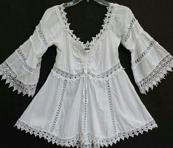 """CROCHET LACE Boho Tunic Top Blouse Lk Free People Pre-owned, great condition. Vintage (?) white peasant blouse features crochet lace trim neckline and hem, adjustable ruch cinching at bust, elasticized neckline and upper back, cutout lace inserts down the body and sleeves. Love this top but it's a true to size Medium. If you're a small, it will be too big and the shoulders will slide down. 55% cotton, 45% rayon. Size Medium. Underarm across : 15.5"""" Sleeve : approx 14"""" underarm to end Length…"""
