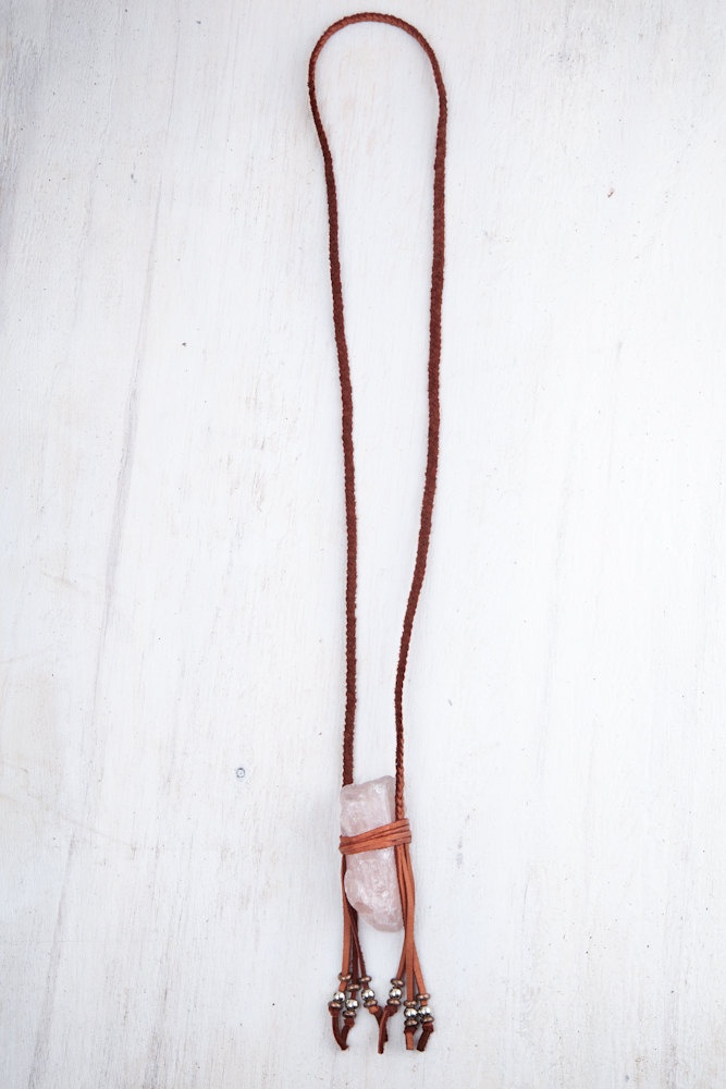 Large rose quartz crystal stone wrapped in braided leather fringe