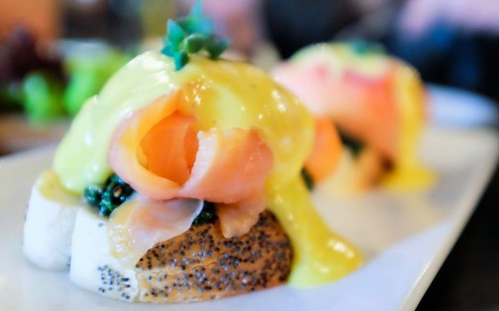 Perfectly poached eggs on poppy seed toast with sauteed spinach & grated cheese, crowned with a choice of smoked salmon, turkey bacon or beef bacon, coated in creamy hollandaise sauce at The Bee, Publika.
