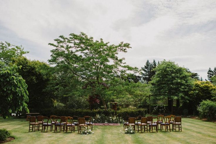 bohemian garden wedding ceremony with vintage chairs