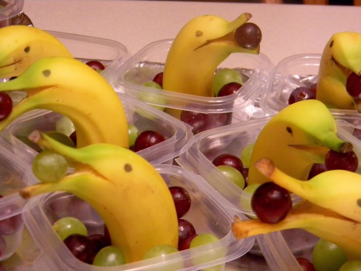 Banana Dolphins! ~ Use unbruised bananas, wash & dry gently. Use a sharp knife and cut the stem all the way to the banana and a little past to make a smile, Put a small grape into the opening. Cut the bottom half off a little past the middle. Stick the banana in the cream cheese to keep it standing. Add grapes around the dolphin. Brush lemon juice into the opening so it doesn't brown. Add eyes w/ an edible marker, cloves, raisins, chocolate chips, or frosting.