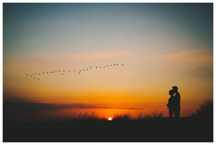 Silhouette of couple on a hill at sunset with birds flying. www.ellen-richardson-weddings.com/blog