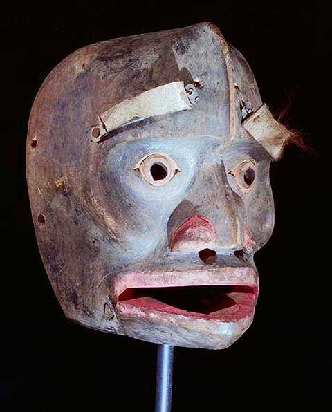 """Naxnok Mask    The naxnok (spirit) """"W'atsx"""" represents the animal spirit of the Fisher. This naxnok enters into people and temps them into the woods where they become lost forever. When a performer appeared as W'atsx- at gatherings, he wore a suit of marmot skins and wielded wooden claws. He danced, sounding a concealed whistle, wiggling his moveable eyebrows and lower jaw. He then struck out at certain chiefs with his claws, sometimes causing injury.  Acquired at Laxgalts'ap, 1912"""