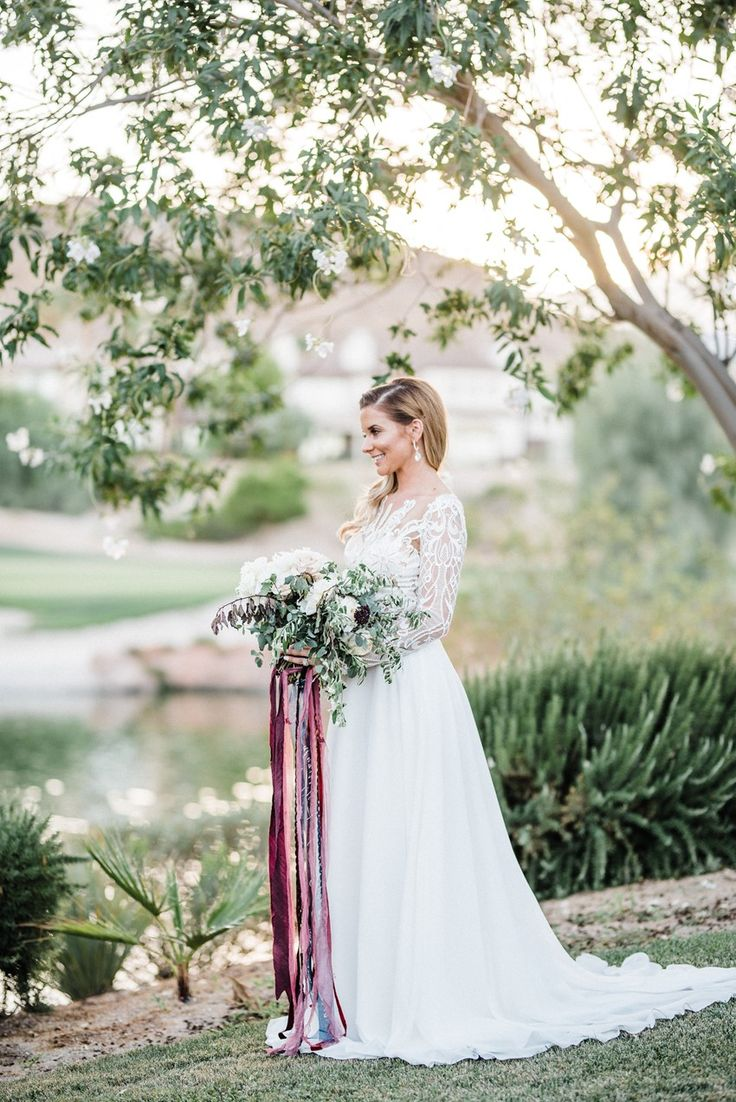 Bride in Long Sleeve Wedding Dress with Bouquet & Trailing Ribbons