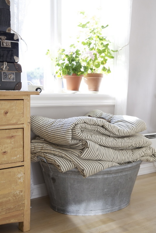 ticking quilts folded in galvanized bin