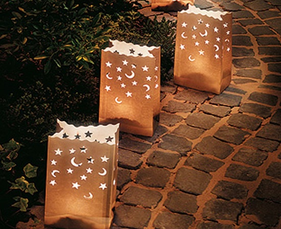 romantic lighting with punched paper bags. Weight the bottom with sand and place  a votive