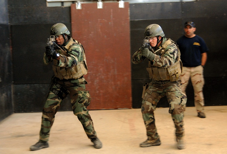U.S. Navy SEAL qualification training students engage targets during close quarters combat training.