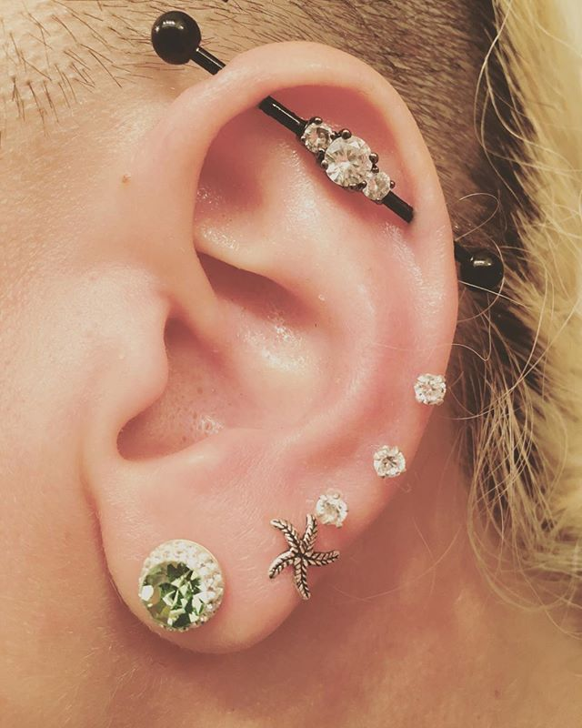 """Bring not just double, but triple the sparkle with this industrial barbell earring. Measuring a length of 1 7/16"""", the straight black IP over 316L surgical grade stainless steel barbell features a cluster of three clear cubic zirconia gems at its center."""