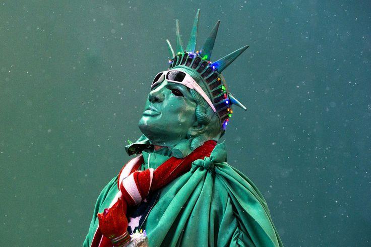 Seorang seniman jalanan mengenakan kostum patung Liberty di Times Square, New York.