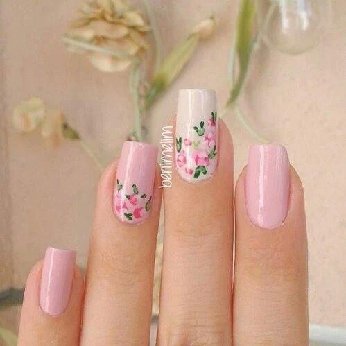 Manicura en rosa dedo medio en blanco y sobre cama de la uña anular y medio flores con tinta roja y verde