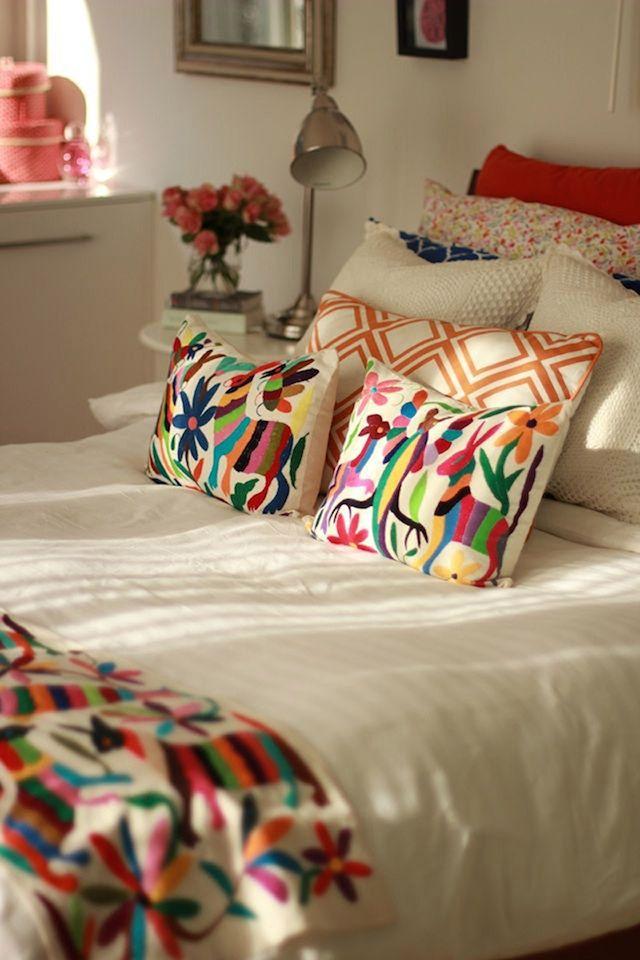Cama con cobertor blanco, piecera y par de cojines con ilustraciones bordadas en múltiples colores, en la cabecera almohadón con…