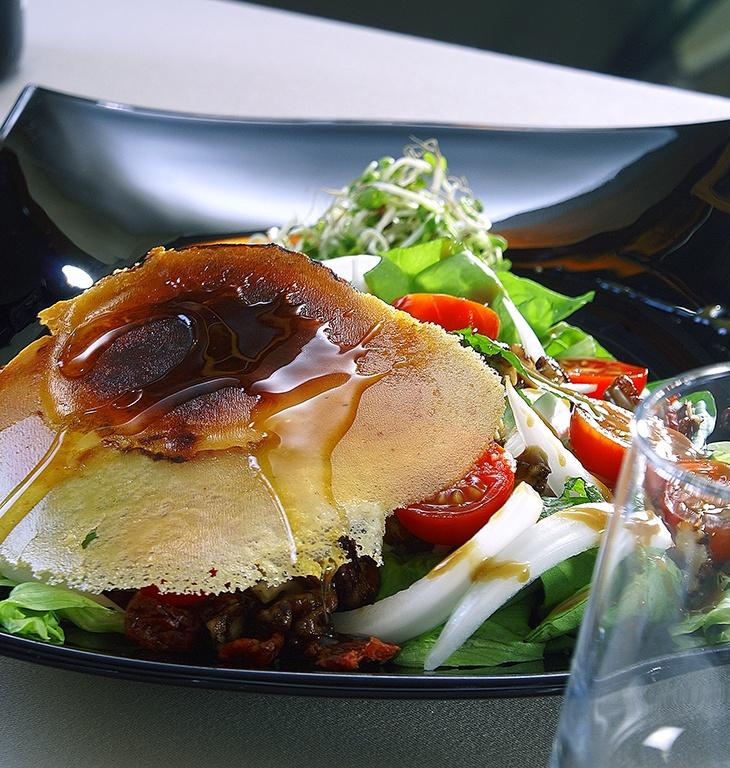 Ensalada con creepe y queso de cabra, miel y frutos secos garrapiñados