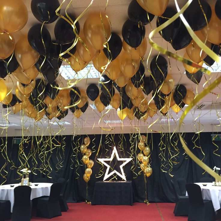 Black and gold balloon ceiling decoration with gold light up star by Boutique Blooms Floral Design & Styling. Black and gold theme party. new years eve party.