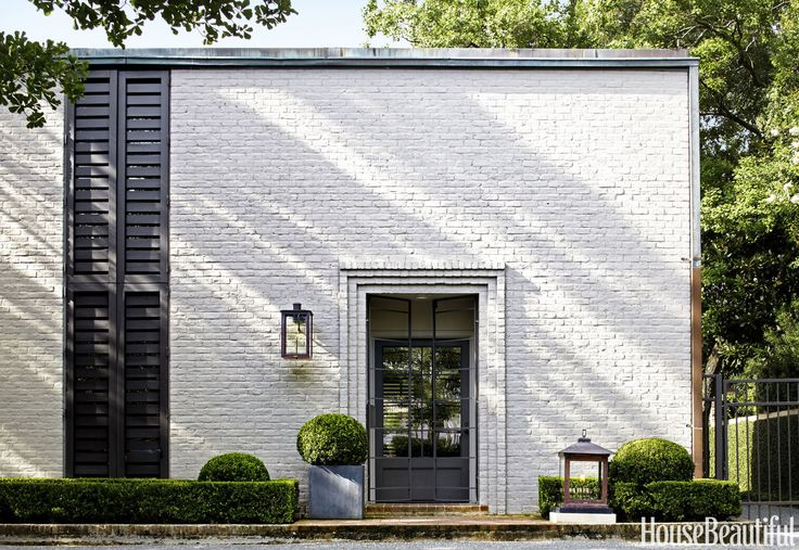 A Retro Home Went Back to the Future Thanks to a Sleek Update Built in 1961 - MidCentury Houston Home updated by MacAlpine architects - white exterior with steel shutters and door