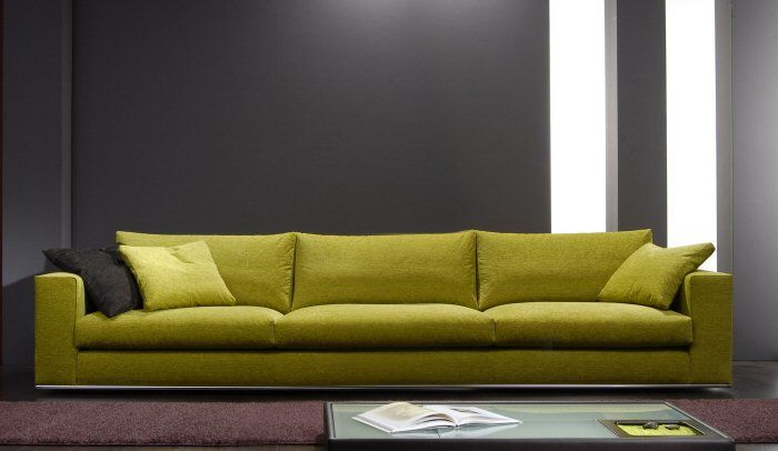 Divano verde senape abbinato al colore grigio della parete e al tappeto colore malva
