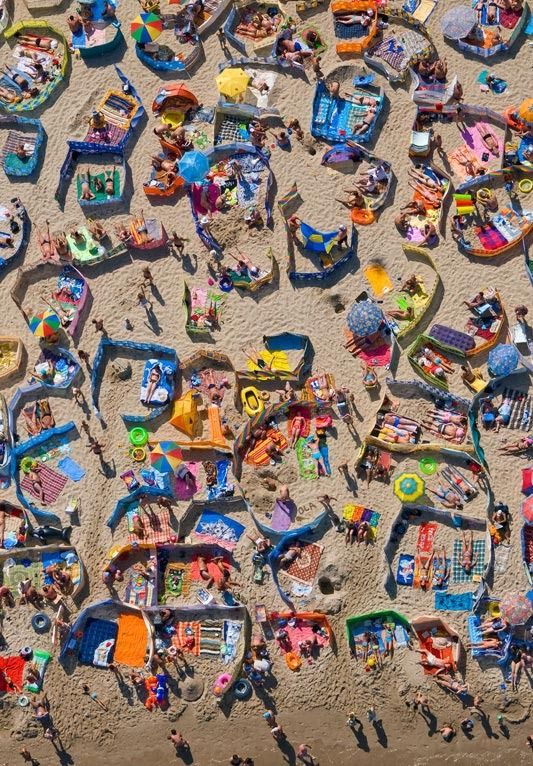 """In 2008, Kacper Kowalski's series """"A Day on the Beach"""" was awarded the second prize in the World Press Photo. These photographs were captured over the course of a day at Władysławowo, a small resort on the Baltic coast. The first few arrivals are seen as brightly colored anomalies on the sandy beach. (...) Later in the day, the seaside becomes a colorful mosaic – towels, umbrellas, cabanas, and sunhats dominate the scene.(From http://culture.pl/)"""