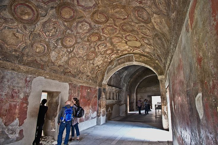 Intricate frescoes on the walls and vaulted ceiling of the Stabian Baths in Pompeii, the oldest of the bathhouses in the ancient Roman city that was destroyed by the 79 AD eruption of Mount Vesuvius. The walls are decorated with plain white and red frescoes, while the vaulted ceiling features elaborate polychrome designs that incorporate rosettes, cupids, and figures of Bacchus, the Roman God of wine and bacchanalia.