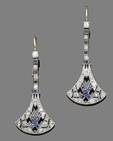 An early 20th century pair of sapphire and diamond pendent earrings Of openwork inverted lotus shape, millegrain-set throughout with old brilliant and single-cut diamonds and calibré-cut sapphires, to an articulated line surmount of old brilliant-cut diamonds and square-cut sapphires, diamonds approx. 1.00ct total, later fitting, length 4.6cm. (hva)