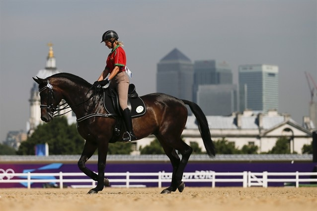 Alena Tseliapushkina of Belarus rides her horse Passat in front of the skyline of Canary Wharf during a training session at Greenwich Park, the site for the equestrian and modern pentathlon events July 25. The horse & rider did poorly in the dressage event July 28.
