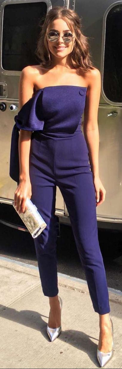 Who made Olivia Culpo's blue off the shoulder jumpsuit, silver pumps, white clutch handbag, and round sunglasses?