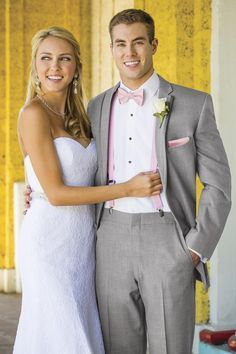 Grey wedding suit from Jims Formal Wear available at Celebrations Bridal and Prom - paired with pink suspenders, bowtie, and pocket square