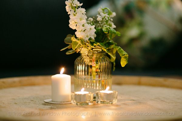 floral centrepieces on wine barrels for wedding reception styling idea.