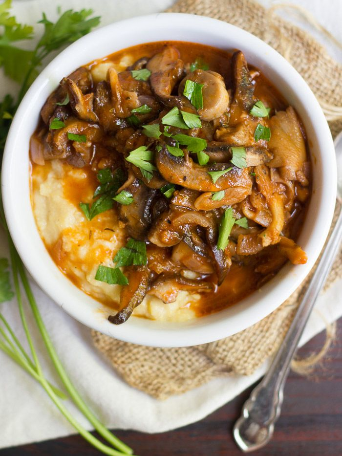 Creamy polenta is topped with a wild mushroom that's ragú cooked up in an herbed red wine tomato sauce to make this irresistible vegan bowl of coziness!