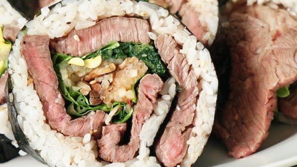 ビデオ指示付きレシピ: 大判のミディアムに焼いたステーキ肉を大胆に巻物に! 材料: 牛肩ロース ステーキ肉 400g, 塩 小さじ1/2, 胡椒 小さじ1/2, サラダ油 小さじ1, ご飯 250g, 白ごま 大さじ1, のり 1.5枚, ナムル 適量, サンチュ 4枚, 焼肉のたれ 適量