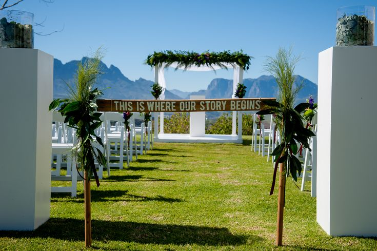 Wedding ceremony set up with a white wooden gazebo, wimbledon chairs, plinths and greenery as floral