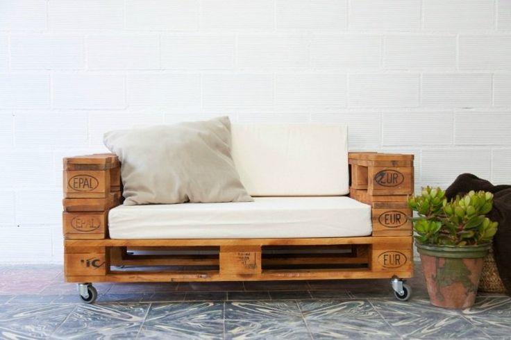 canapé en palette de bois rembourée à roulettes avec coussins