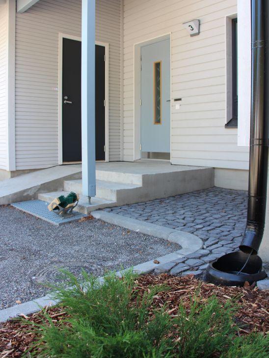 Upotettava kadunreunakivi rajaa istutusalueet ja kiveykset kivituhka-alueista. Louhikivi elävöittää sisäänkäyntiä.