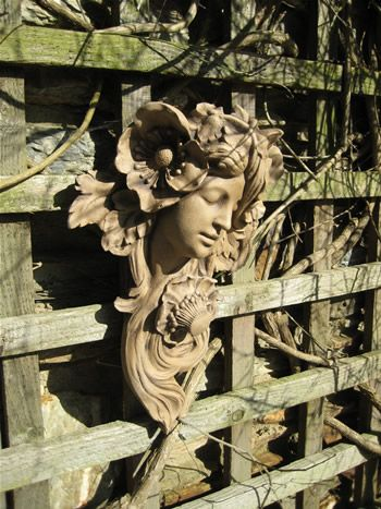 Art Nouveau sculpture on a a garden wall.
