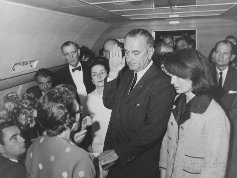 1963~ Lyndon Johnson taking the oath of office to become the 36th President of the US.  There's Jackie still in her blood-splattered pink suit.