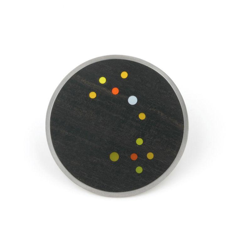 Confetti grote broche van ebbenhout. De broche is gevat in een ruime (driehoekige rand) zilveren rand. Ontwerp Marion Pannekoek | The Jewelry Story