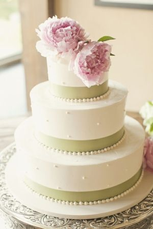 wedding cake with pearl accents in white and sage green topped with fresh flowers