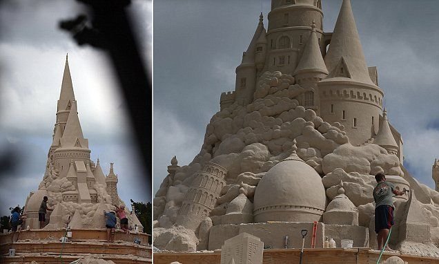 Sand sculptors work to create the world's tallest sand castle
