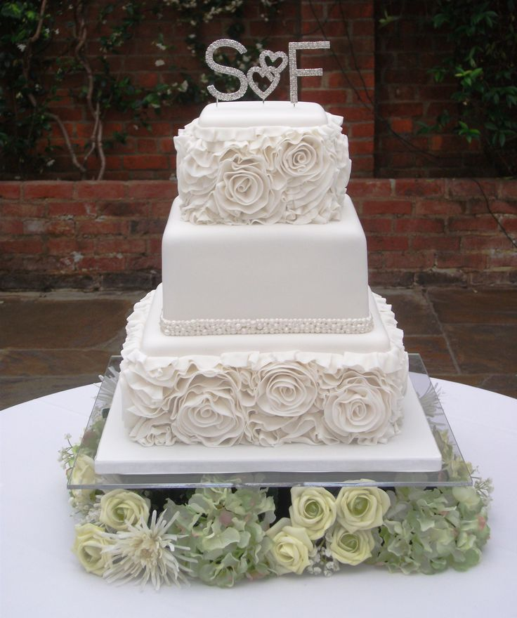 Square three tier wedding cake, with sugar ruffles around the top and bottom tiers, and a piped lustred pearl band around the middle tier.