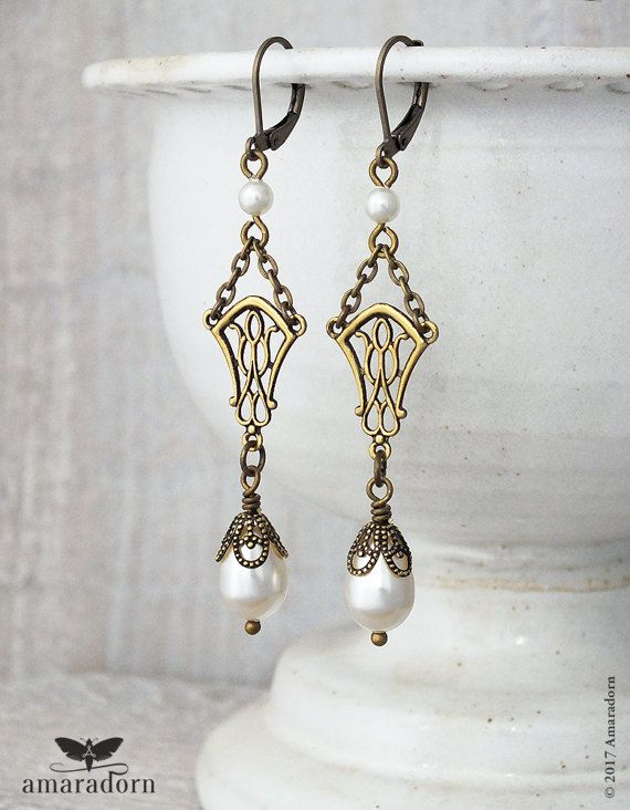Wonderfully elegant, vintage inspired earrings featuring delicate antiqued brass filigrees which echo the organic style of the Art Nouveau period (early 1900s France) and the wonderful jewellery designs of Alphonse Mucha. Combined with superior quality cream/ivory Swarovski® Crystalized™ Pearl peardrops, antiqued brass filigree bead caps and bronze chain. Attached to bronze finish lever back earwires for pierced ears. These earrings are designed and handmade by Amaradorn using Swarovski...