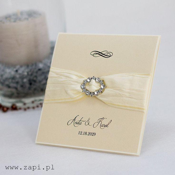 Luksusowy projekt zaproszenia ślubnego z kremową wstążką dekoracyjną i srebrną klamrą.