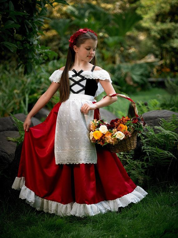 Red Riding Hood Peasant Costume: Leotard Bodice has center panel of white velvet & criss crossed lacing. White ruffled sleeves are lined in eyelet cotton with lace ruffle overlay. Satin Skirt is embellished with a double ruffle of embroidered eyelet with white ruffled lace for impression of a petticoat. Cotton apron is eyelet cotton gathered to a waistband that ties in the back. The apron is trimmed with a double eyelet ruffle with lace overlay. Rose Garland Headband comes in organza bag.