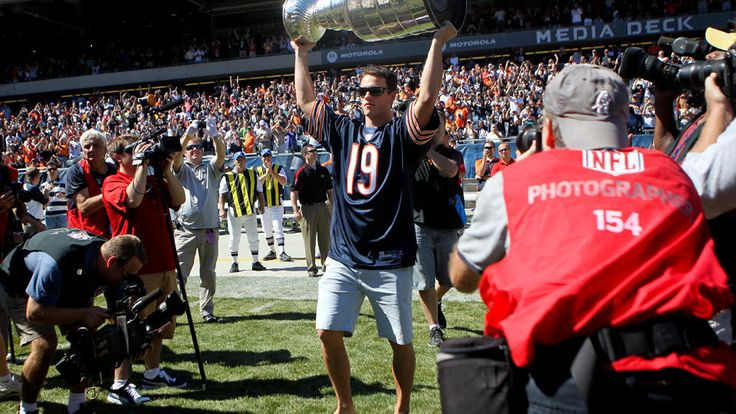 Jonathan Toews walks onto the Soldier Field turf holding the Stanley Cup.