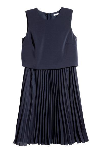 Knælang kjole i vævet kvalitet. Kjolens overdel er crepet med lynlås bagtil. Plisseret underdel. Med for.