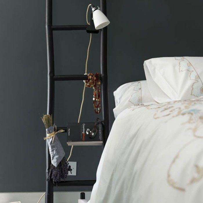 Ladder als nachtkastje. Een nachtkastje hoeft natuurlijk niet altijd echt een kastje te zijn. Hier staat een decoratieve ladder naast het bed. Eventuele tijdschriften hang je gewoon over de sporten van de ladder heen.